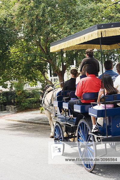 Rückansicht einer Gruppe von Personen in einem Pferdewagen unterwegs