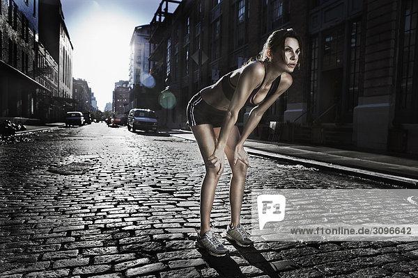 Frau stehend mit den Händen auf Knien nach Übung