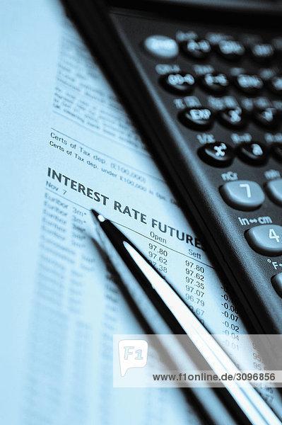 Finanzieller Rechner und einen Stift auf eine Wirtschaftszeitung