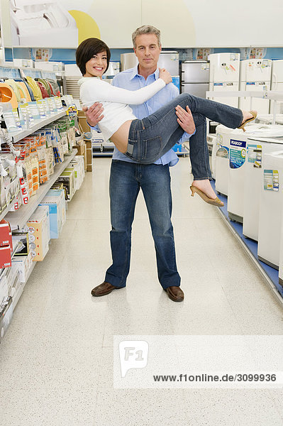 Father carrying his daughter in a supermarket