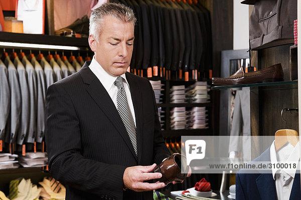 Kaufmann auswählen Schuhe in einem Bekleidungsgeschäft