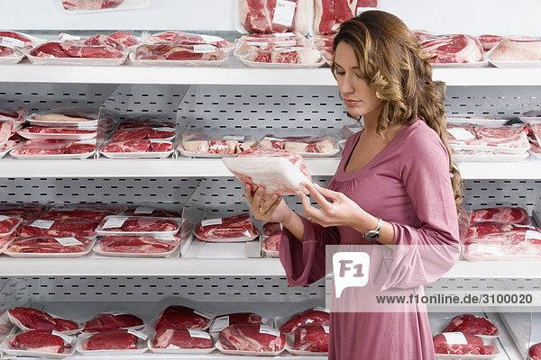 Frau verpackten Fleisch in einen Supermarkt auswählen