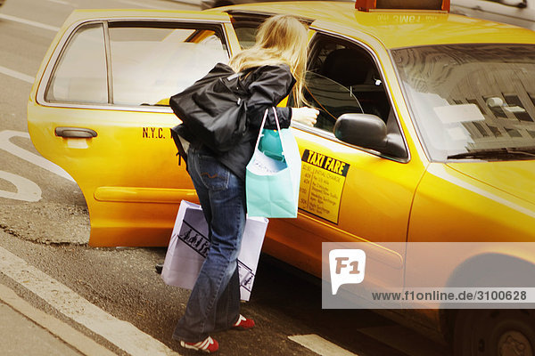 Rear view of a woman standing near a yellow taxi