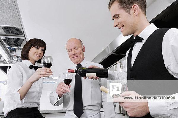 Kellner Gießen Wein in die Gläser seiner Kollegen