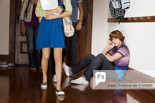 Teenager sprechen auf einem Mobiltelefon mit seinen Freunden in der Schule-Korridor