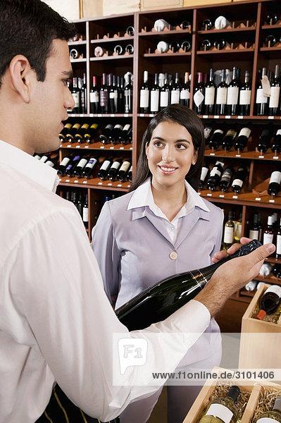 Verkaufssekretärin eine Weinflasche neben lächelnd geschäftsfrau hält