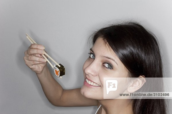 Lächelnde Frau halten Sushi-Rolle mit Stäbchen