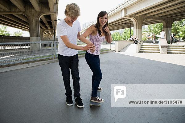 Boy helping girlfriend to skate