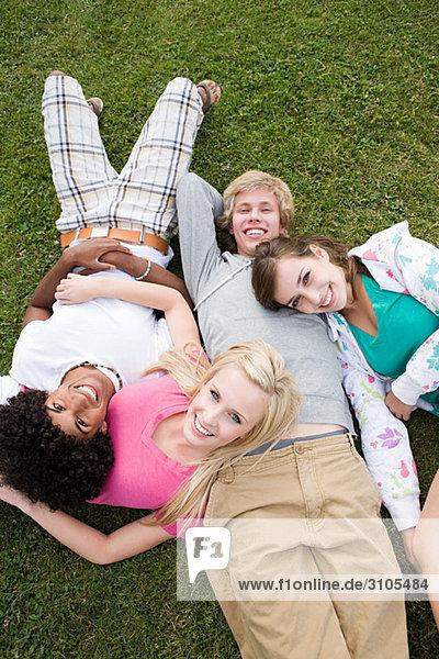 Teenage friends lying on grass