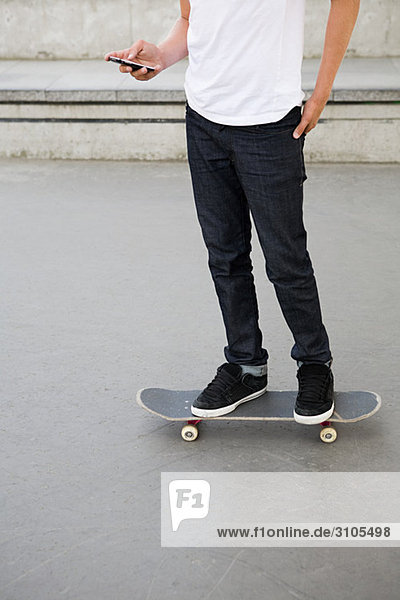 Teenage boy on skateboard with cellphone
