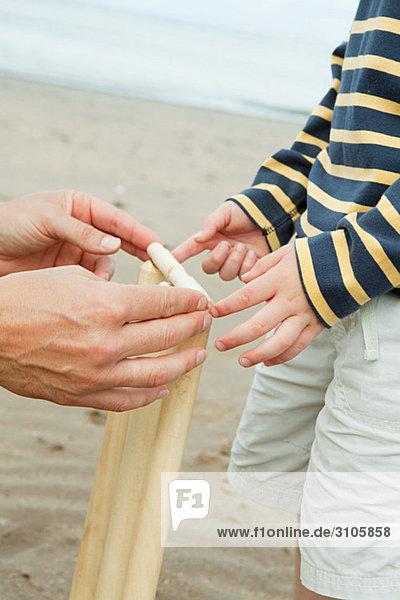 Erwachsene und Kinder beim Aufstellen von Grillenstümpfen