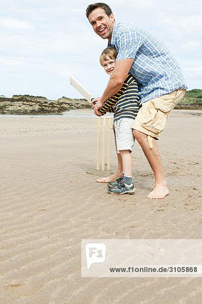 Vater und Sohn spielen Cricket am Strand