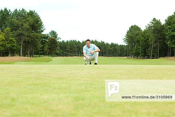 Männlicher Golfspieler auf dem Fairway kauernd