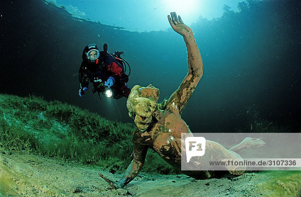 Scuba diver discovering Nixie of King Ludwig in the Badersee  Germany  Bavaria  underwater shot
