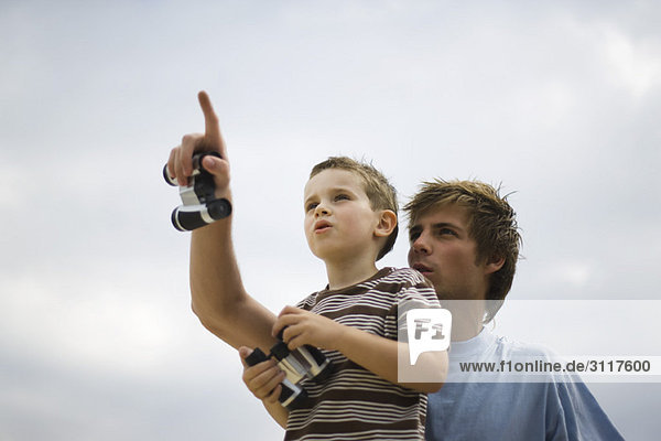 Father and son looking up at sky  holding binoculars