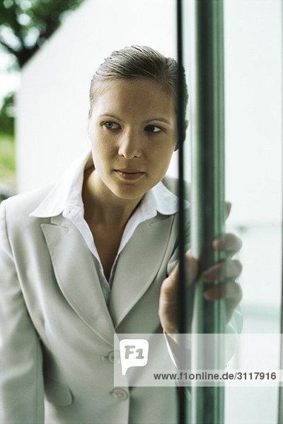 Businesswoman entering building  hesitantly opening door