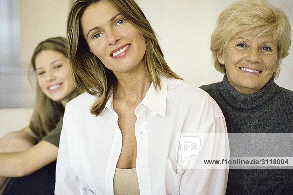 Frau mit älterer Mutter  jugendliche Tochter im Hintergrund
