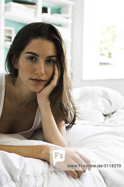 Woman lying on bed leaning on elbow looking at camera