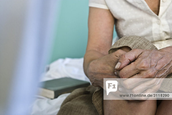 Woman's hands clasped on knee  close-up
