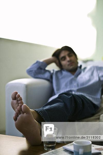 Mann auf Sofa sitzend mit Füßen oben auf dem Couchtisch