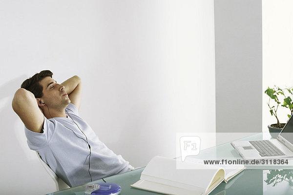 Der Mann am Schreibtisch lehnt sich mit den Händen hinter dem Kopf zurück  hört Kopfhörer und pfeift.