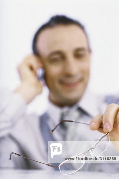 Geschäftsmann am Telefon  der eine Brille in der Hand hält.