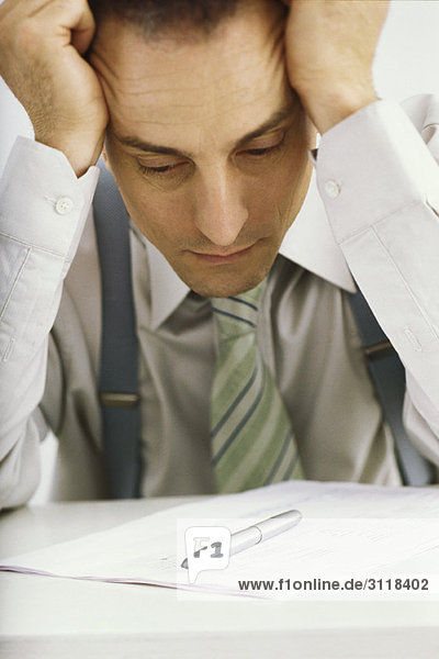 Mann hält Kopf  starrt auf Dokument