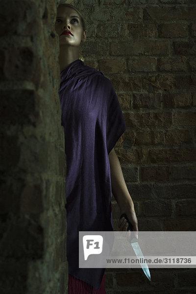 Frau steht in dunkler Ecke mit Messer in der Hand  schaut nach oben