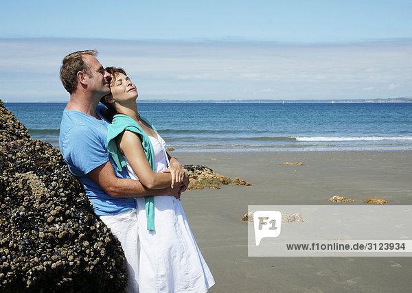 Paar umarmt sich am Strand  angelehnt an einen Felsen  Seitenansicht