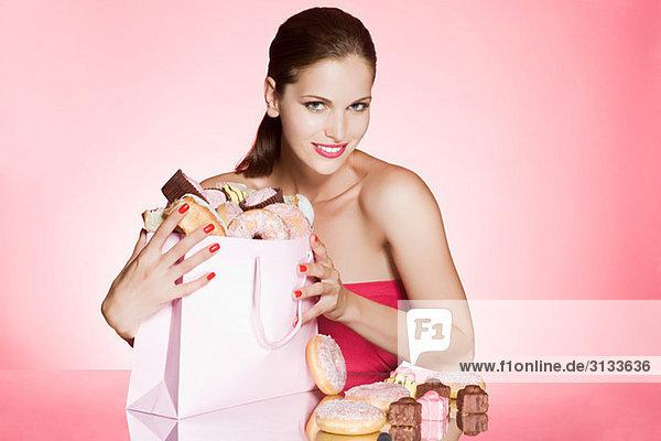 Junge Frau mit Tüte Kuchen und Donuts