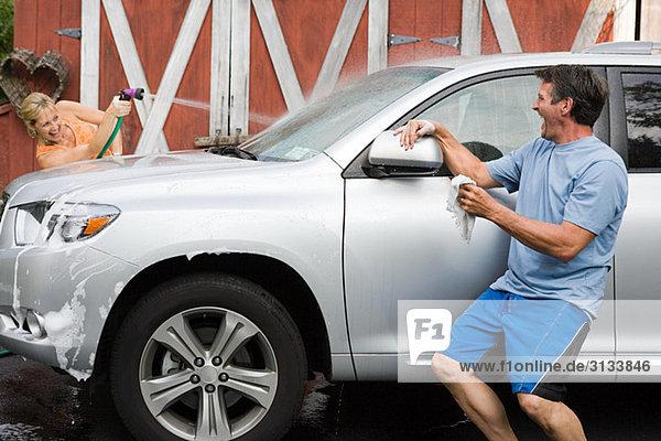 Paar mit Spaß beim Auto waschen