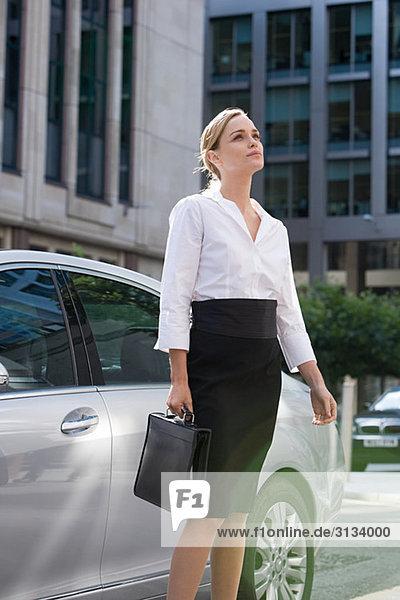 Geschäftsfrau steht beim Auto