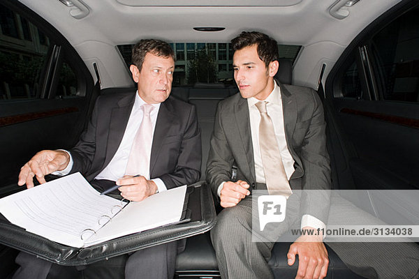 Two businessmen in the back of a car