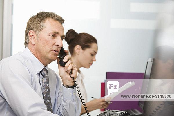 Ein älterer Geschäftsmann am Telefon