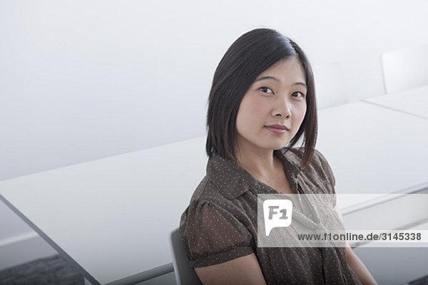 Geschäftsfrau sitzend im weißen Zimmer