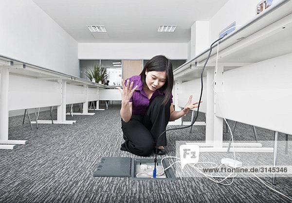 Frau kämpft mit Hi-Tech-Kabeln