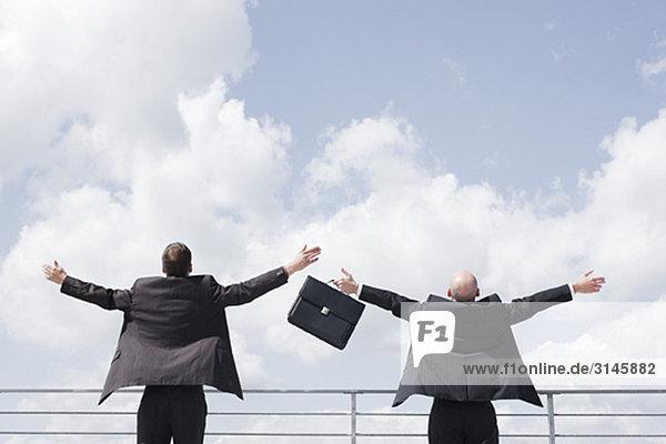 zwei Geschäftsmänner  die Waffen in den Himmel werfen