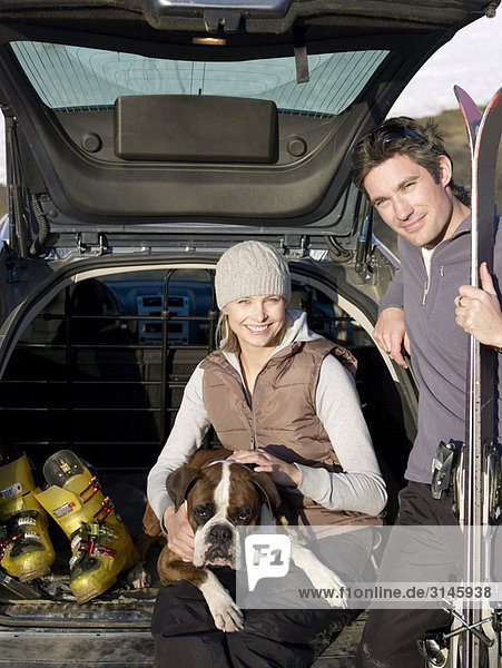 man and woman in car with dog
