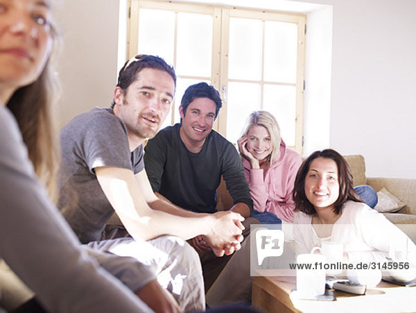Freunde lachen im Chalet-Wohnzimmer
