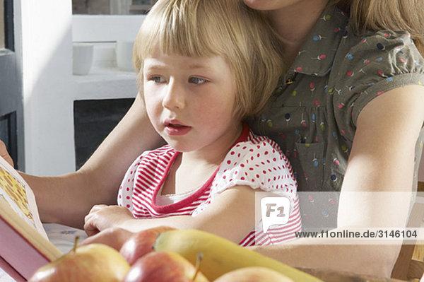 Mädchen auf Müttern Schoß Lesebuch