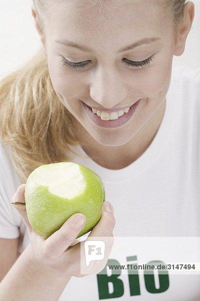 Frau isst grünen Bio-Apfel