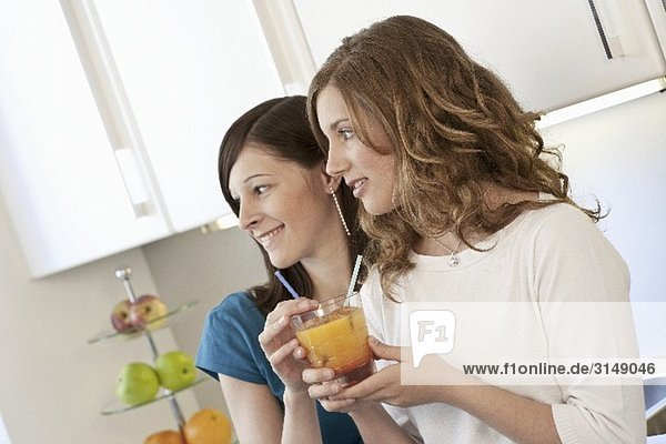 Zwei junge Frauen trinken einen Fruchtcocktail