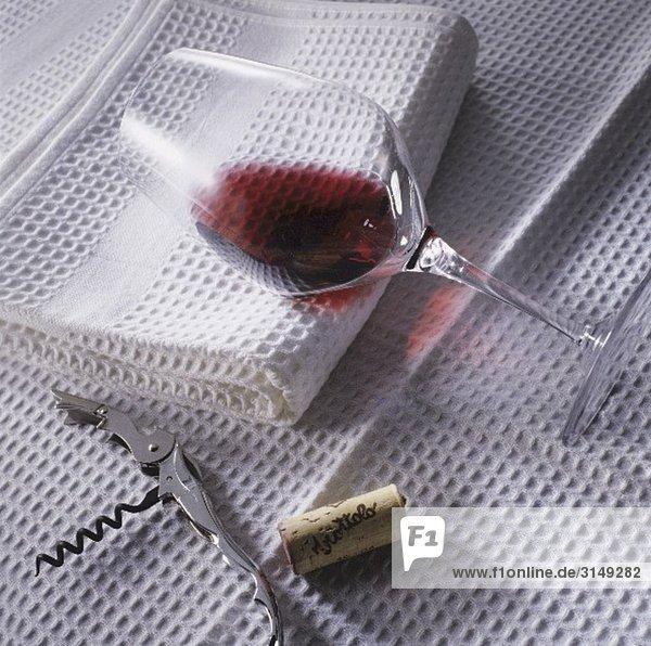 Glas mit Rotwein auf weissem Tuch Glas mit Rotwein auf weissem Tuch