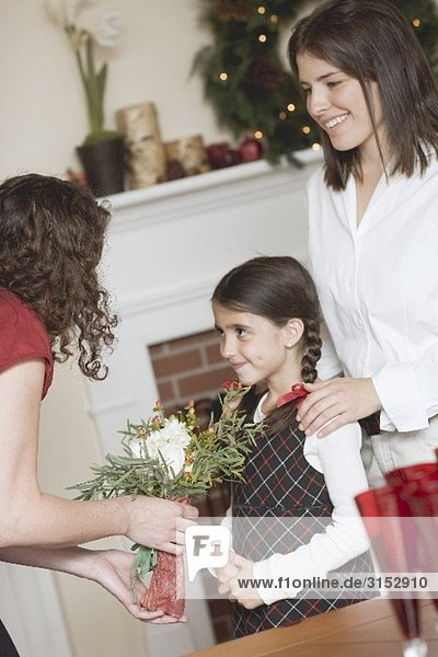 Two women and small girl in front of fireplace (Christmas)