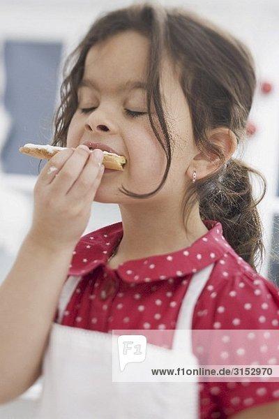 Kleines Mädchen isst selbst gebackenes Weihnachtsplätzchen