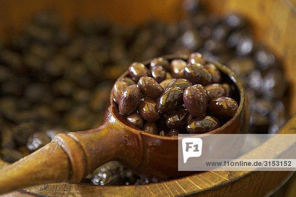 Eingelegte Oliven in Holzfass und Kelle