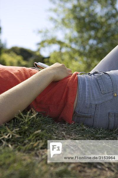 Junge Frau auf Boden anhören von MP3-Player  Mitte Abschnitt