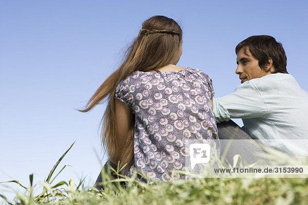 Junges paar sitzen auf Gras mit Konversation