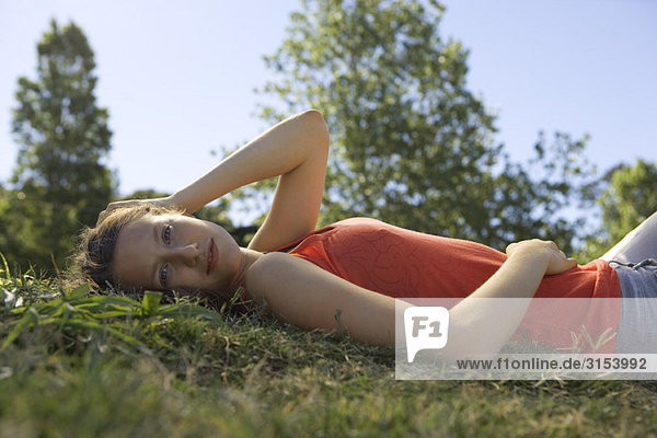 Junge Frau liegen auf Rücken im Gras  Portrait