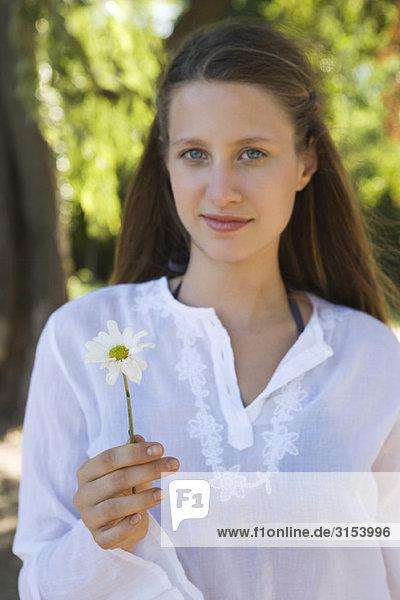 Junge Frau hält Blume  portrait